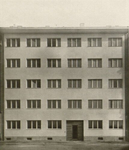 Fünfgeschossiger Bau mit sehr flachem Dach und extrem gleichmäßiger Fensterreihung. Der gerade ausgeschnittene Eingang ist die einzige Unterbrechung.