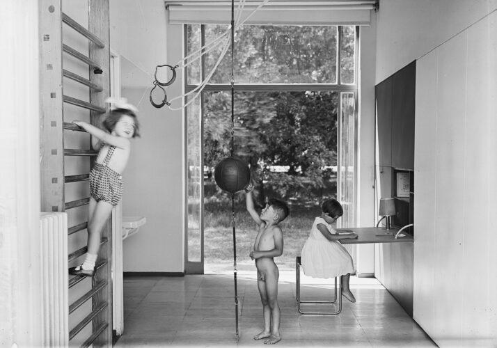 In einem durchgangartigen Zimmer mit großer Tür zum Garten spielen zwei Kinder an Sprossenwand und aufgehängtem Medizinball, eines sitzt an einem ausgeklappten Schreibtisch.