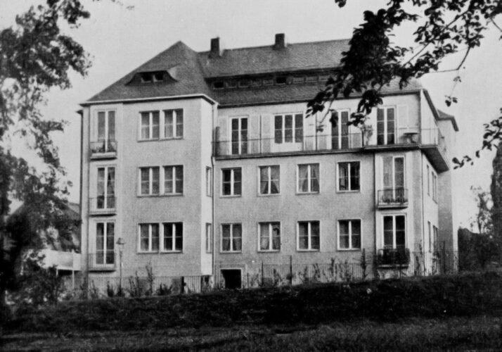 Dreigeschossiger rechteckiger, kompakter Bau mit stehenden Fensterformaten und Walmdach mit langer Schleppgaube.