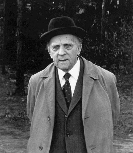 Hans Richter im Alter von 86 Jahren mit Hut, Krawatte, Sakko und Mantel.