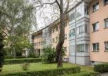 Die verglasten Loggien werden über die Stockwerke gebündelt und kontrastieren mit dem rötlichen Putz und dem grünen Vorgarten.