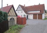 Foto von rechts auf den weiß verputzte Garagenbau in gutem Zustand mit zwei eckigen braunen Garagentoren und mit Ziegeln gedecktem Dach. Vorn links angeschnitten das
