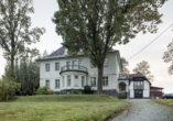 Die erhöht stehende, weiß verputzte Villa mit zentralem Runderker und Walmdach hinter einem rechts stehenden belaubten Baum. Rechts führt ein gepflasterter Weg zu einem Nebengebäude mit Fachwerkschmuck.