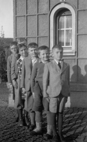 Čtyři chlapci a dívka ve věku od 10 do 12 let jsou seřazeni jako stupínky. V pozadí je vidět roh Richterova domu.