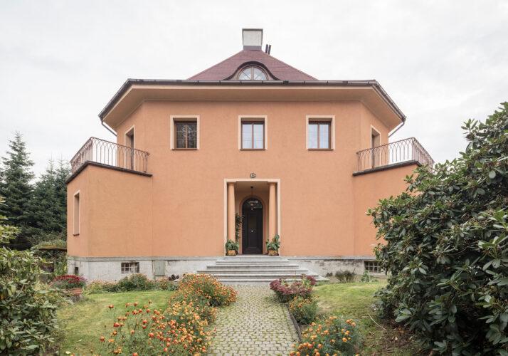 Fotografie zpevněné zahradní cesty vedoucí přímo k předním dveřím oranžově omítnutého domu v mírném podhledu. Vpravo a vlevo vyčnívají malé arkýře s balkony, stanová střecha má komín uprostřed. Vstupní dveře jsou lemovány válcovými sloupy.