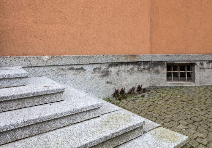Fotografie schodů ke vchodu, které vyčnívají šikmo do obrázku zleva. Vpravo dochovaný teracový sokl pod oranžově omítnutou zdí.