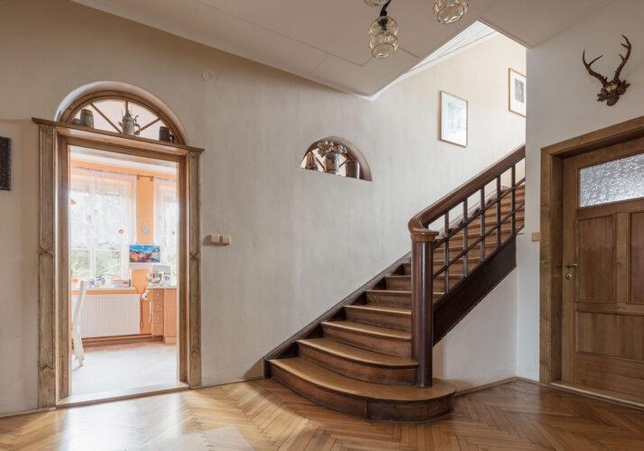 Fotografie vstupní haly, v pohledu jsou otevřené dveře vedoucí do obývacího pokoje a schodiště vedoucích do patra. Parkety, dřevěné schody, dřevěné dveře s půlkruhovými světlíky.