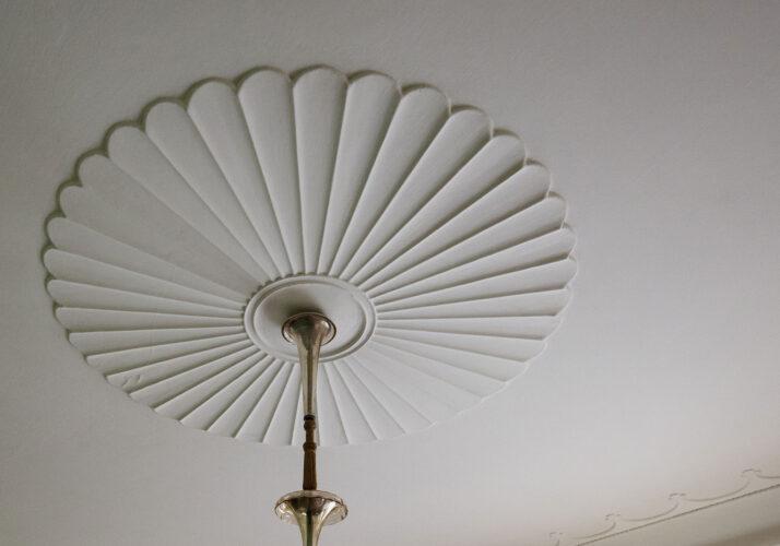 Fotografie štukovitého obrazce na stropu připomínajícího ventilátor z prostředka visí lustr.